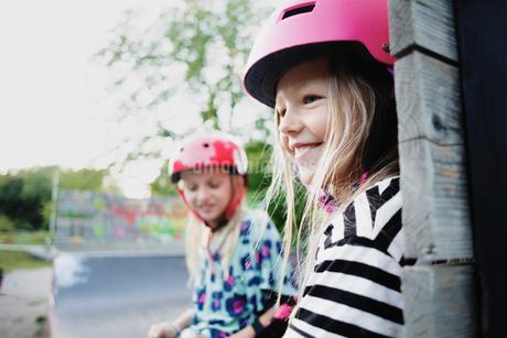 Smiling girl wearing helmet sitting with friend on edge of skateboard rampの写真素材 [FYI02141821]