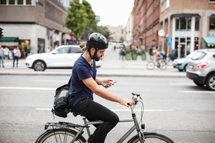 Side view of man using mobile phone while riding bicycle on city streetの写真素材 [FYI02141826]