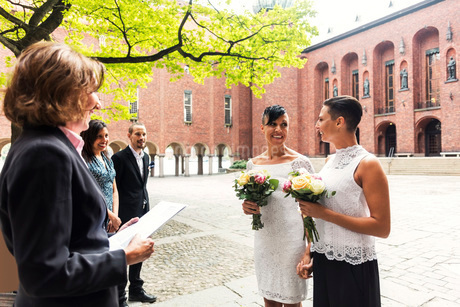 Happy lesbian couple standing in front of female priest for wedding ceremonyの写真素材 [FYI02141870]