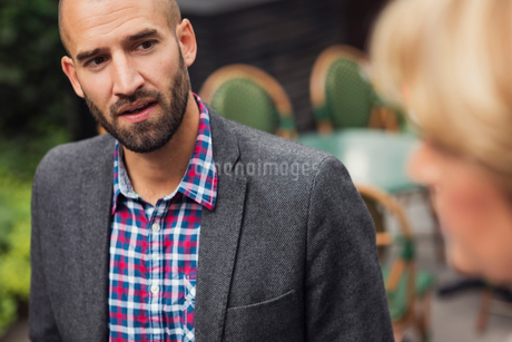 Mid adult businessman talking with female colleague at office yardの写真素材 [FYI02141891]