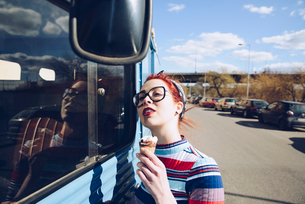 Young woman holding ice cream cone while standing by mini van on streetの写真素材 [FYI02141902]