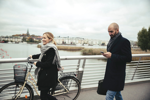 Smiling businesswoman with bicycle walking by businessman on bridgeの写真素材 [FYI02141919]