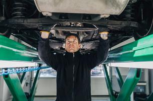 Male mechanic examining car on hydraulic lift in auto repair shopの写真素材 [FYI02141922]