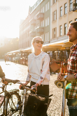 Happy friends with skateboard and bicycles talking on city streetの写真素材 [FYI02141927]