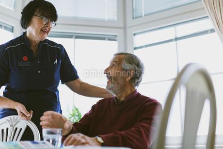 Senior man talking to female caretaker at homeの写真素材 [FYI02141929]