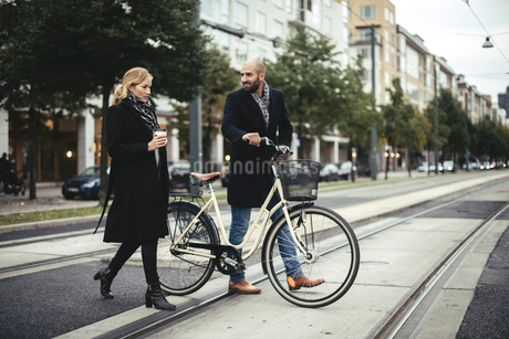 Full length of business people with bicycle crossing city streetの写真素材 [FYI02141933]
