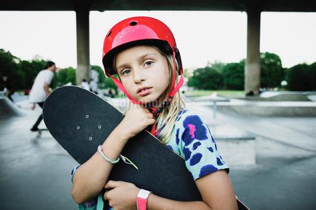 Portrait of girl wearing red helmet holding skateboard at parkの写真素材 [FYI02141939]