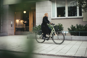 Full length of mid adult businesswoman riding bicycle by city buildingの写真素材 [FYI02141986]