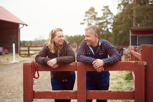 Smiling mature couple looking at each other while leaning on fence in farmの写真素材 [FYI02142016]