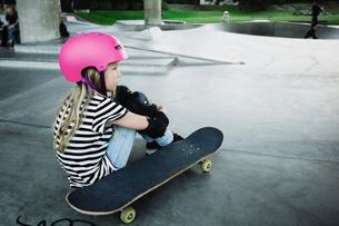 Thoughtful girl wearing pink helmet sitting at skateboard parkの写真素材 [FYI02142020]
