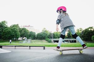 Full length of girl skateboarding at park against clear skyの写真素材 [FYI02142088]