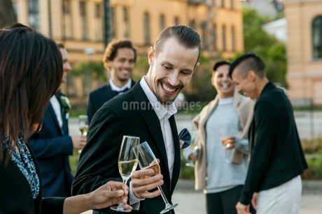 Happy friends toasting champagne during wedding ceremonyの写真素材 [FYI02142106]