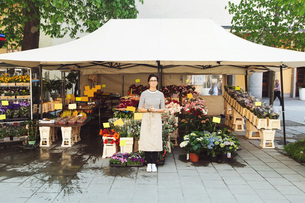 Portrait of female owner standing outside flower shopの写真素材 [FYI02142119]