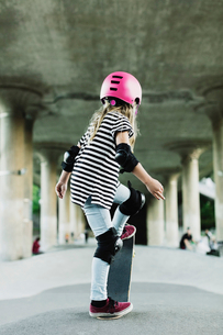 Rear view of girl performing stunt with skateboard at parkの写真素材 [FYI02142134]