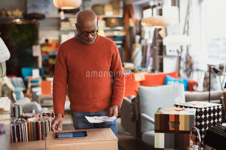 Senior man using digital tablet while reading document at storeの写真素材 [FYI02142165]