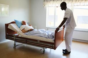 Male nurse adjusting bed while senior man watching TV in hospital wardの写真素材 [FYI02142176]