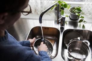 Cropped image of man washing utensils at kitchen sinkの写真素材 [FYI02142183]
