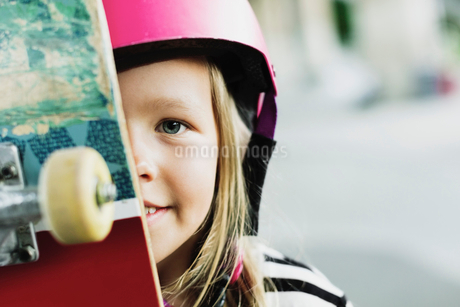 Portrait of smiling girl with skateboard at parkの写真素材 [FYI02142189]
