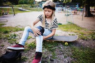 Girl tying kneepad while sitting on skateboard at parkの写真素材 [FYI02142214]