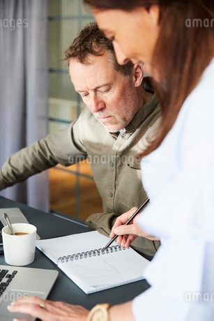 Mature creative colleagues writing in dairy while sitting with laptop at conference table in board rの写真素材 [FYI02142251]