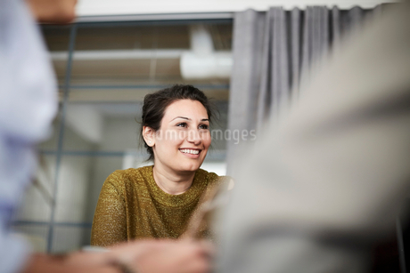 Smiling businesswoman sitting with colleagues in board room during meetingの写真素材 [FYI02142266]
