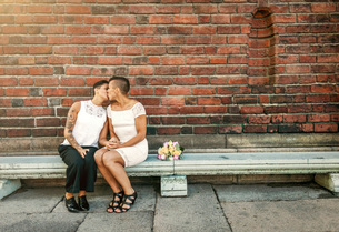 Newlywed lesbian couple kissing while sitting on bench against brick wallの写真素材 [FYI02142321]