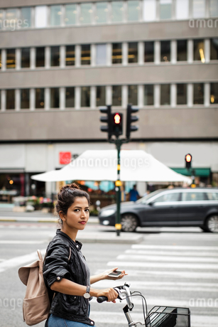 Portrait of woman with bicycle holding mobile phone while standing on city streetの写真素材 [FYI02142348]