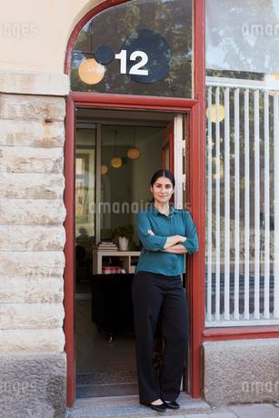 Full length portrait of mid adult businesswoman standing arms crossed in office doorwayの写真素材 [FYI02142366]