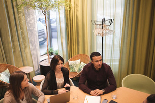 High angle view of business colleagues sitting at conference table against windowの写真素材 [FYI02142416]