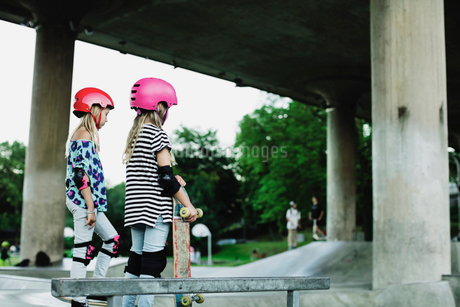 Friends wearing helmets and safety pads standing at skateboard parkの写真素材 [FYI02142422]