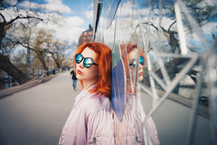Redhead young woman wearing sunglasses while leaning on mosaic wall by streetの写真素材 [FYI02142468]