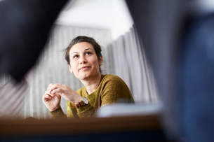 Confident businesswoman looking at female colleague while sitting in board roomの写真素材 [FYI02142471]