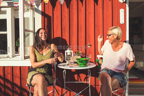 Cheerful mature female friends enjoying summer in back yard on sunny dayの写真素材 [FYI02142483]