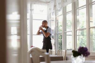 Male owner having coffee and talking on phone while standing by window at cafeの写真素材 [FYI02142486]