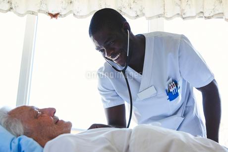 Happy male nurse examining senior man with stethoscope in hospital wardの写真素材 [FYI02142524]