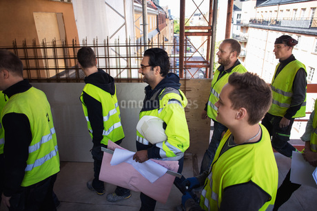 Side view of manger holding blue prints walking with manual workers at construction siteの写真素材 [FYI02142567]
