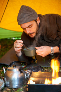 Mid adult man stirring hot tea while relaxing in tent at campsiteの写真素材 [FYI02142577]