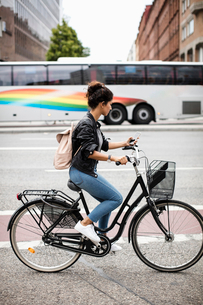 Side view of woman using mobile phone while riding bicycle on city streetの写真素材 [FYI02142579]