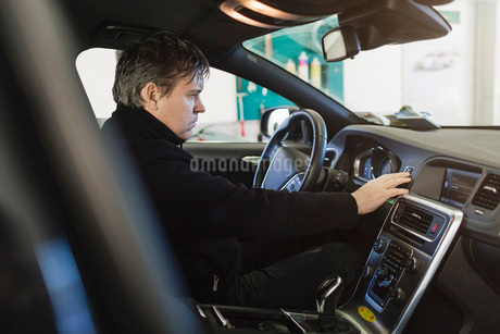 Side view of mechanic examining dashboard in carの写真素材 [FYI02142591]