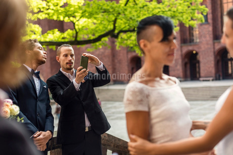 Man photographing lesbian couple during wedding ceremonyの写真素材 [FYI02142604]