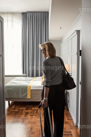Rear view of businesswoman with luggage standing in hotel roomの写真素材 [FYI02142606]