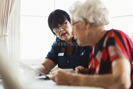 Caretaker assisting senior woman in using digital tablet at homeの写真素材 [FYI02142607]