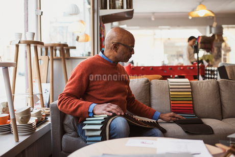 Senior owner arranging fabric swatches while sitting on sofa at storeの写真素材 [FYI02142610]