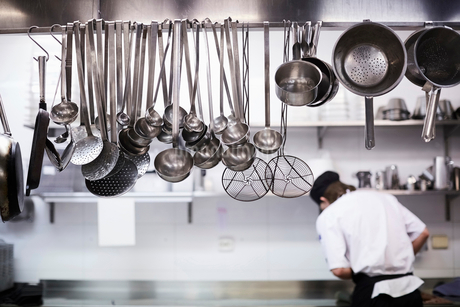 Utensils on metal rack with chef cooking in background at commercial kitchenの写真素材 [FYI02142640]