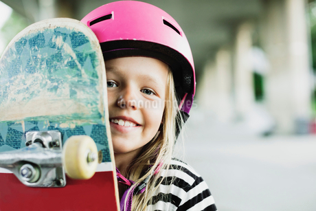 Portrait of happy girl with skateboard at parkの写真素材 [FYI02142649]