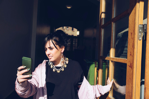Young woman taking selfie with smart phone while standing at doorwayの写真素材 [FYI02142667]