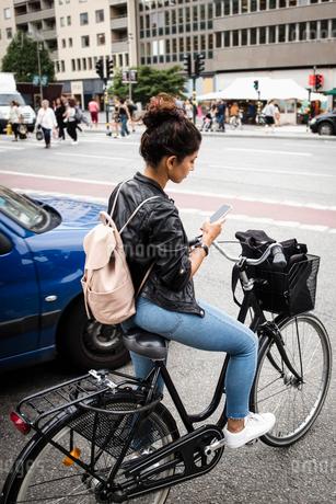 Full length of woman with bicycle using mobile phone while standing at city streetの写真素材 [FYI02142672]