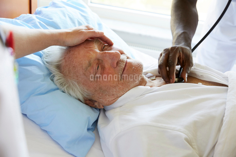 Cropped image of female nurse consoling senior man while male colleague examining with stethoscope iの写真素材 [FYI02142684]