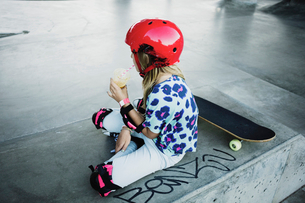 High angle view of girl drinking juice while sitting at skateboard parkの写真素材 [FYI02142726]