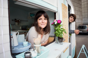 Portrait of male and female owners leaning on food truck windowsの写真素材 [FYI02142727]